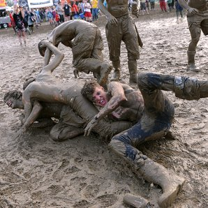 Men wrestling in festival mud.