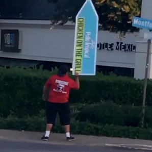 Man holding sign twirling it in Texas