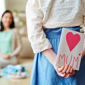Girl hides a mother's day card behind her back